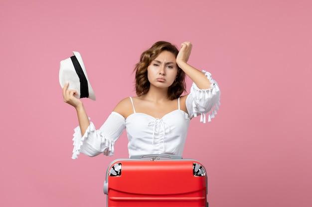 Vorderansicht der jungen frau, die sich auf den urlaub mit roter tasche vorbereitet, die an der rosa wand posiert