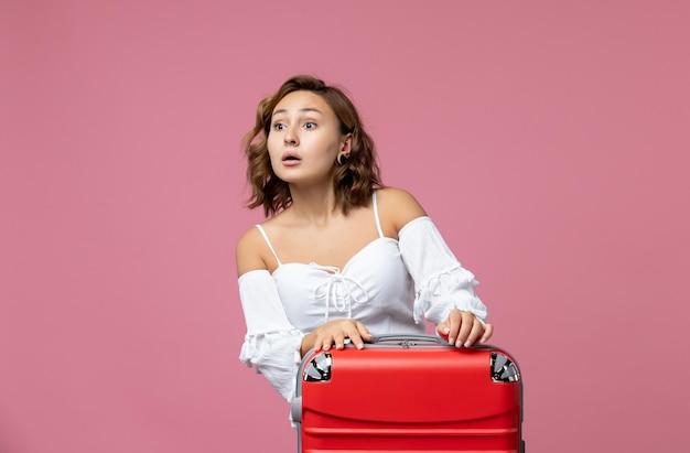 Vorderansicht der jungen frau, die sich auf die reise mit roter tasche an der rosa wand vorbereitet