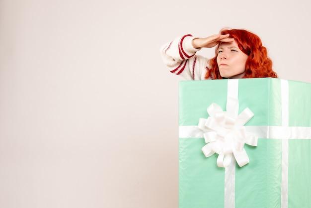 Vorderansicht der jungen frau, die sich innerhalb des weihnachtsgeschenks versteckt, das entfernung auf weißer wand betrachtet