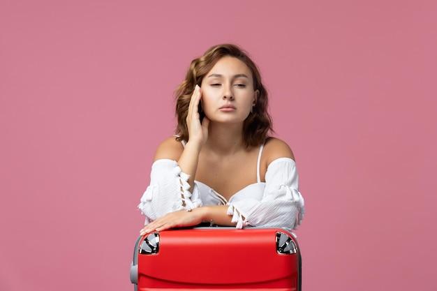 Vorderansicht der jungen frau, die sich mit ihrer roten tasche an der rosa wand auf den urlaub vorbereitet