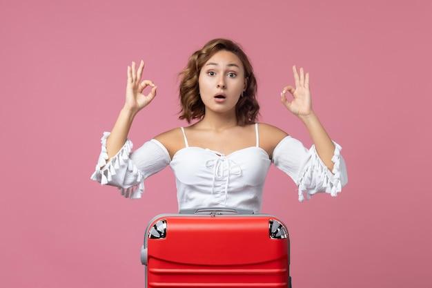 Vorderansicht der jungen frau, die sich mit ihrer roten tasche auf die rosa wand auf die reise vorbereitet