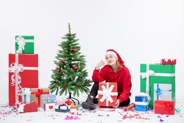 Vorderansicht der jungen frau, die um feiertagsgeschenke auf weißer wand sitzt
