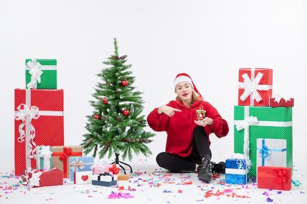 Vorderansicht der jungen frau, die um feiertagsgeschenke sitzt, hält etwas auf weißer wand