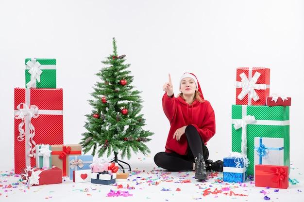 Vorderansicht der jungen frau, die um feiertagsgeschenke sitzt, zählt auf weißer wand