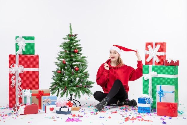 Vorderansicht der jungen frau, die um geschenke auf weißer wand sitzt