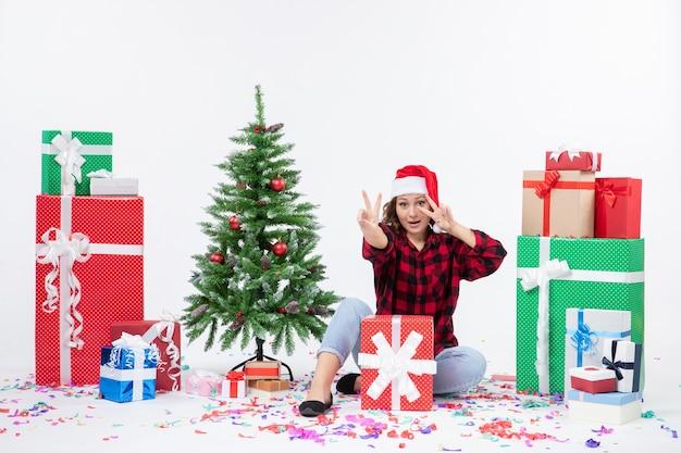 Vorderansicht der jungen frau, die um geschenke und kleinen feiertagsbaum auf weißer wand sitzt