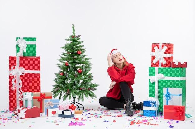 Vorderansicht der jungen frau, die um verschiedene feiertagsgeschenke auf weißer wand sitzt