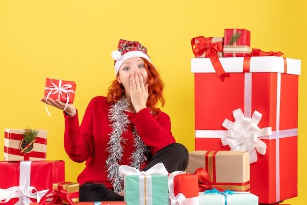 Vorderansicht der jungen frau, die um weihnachtsgeschenke auf gelber wand sitzt