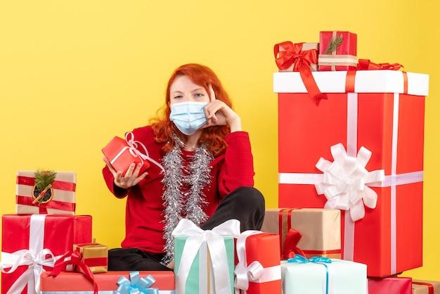 Vorderansicht der jungen frau, die um weihnachtsgeschenke in der maske auf gelber wand sitzt
