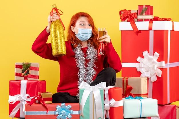 Vorderansicht der jungen frau, die um weihnachtsgeschenke in der maske mit champagner auf gelber wand sitzt