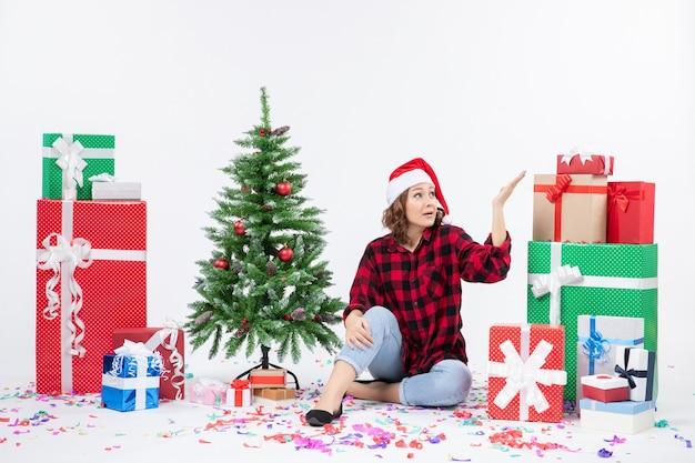 Vorderansicht der jungen frau, die um weihnachtsgeschenke und kleinen feiertagsbaum auf weißer wand sitzt