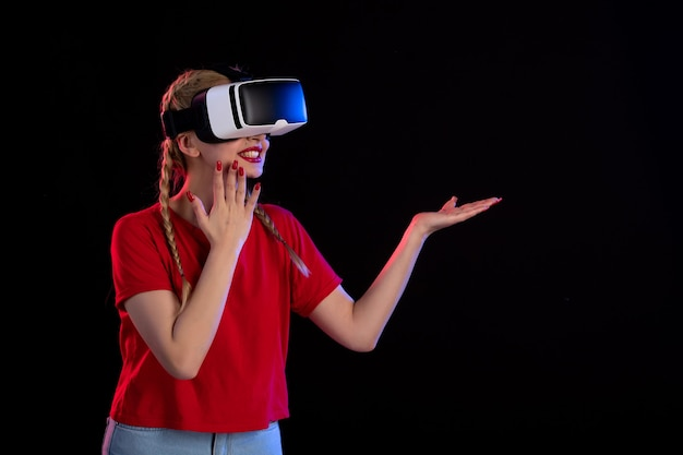 Vorderansicht der jungen frau, die vr auf dunklem spiel-ultraschall-visual spielt