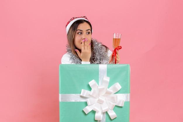 Vorderansicht der jungen frau, die weihnachten mit getränk auf der rosa wand feiert