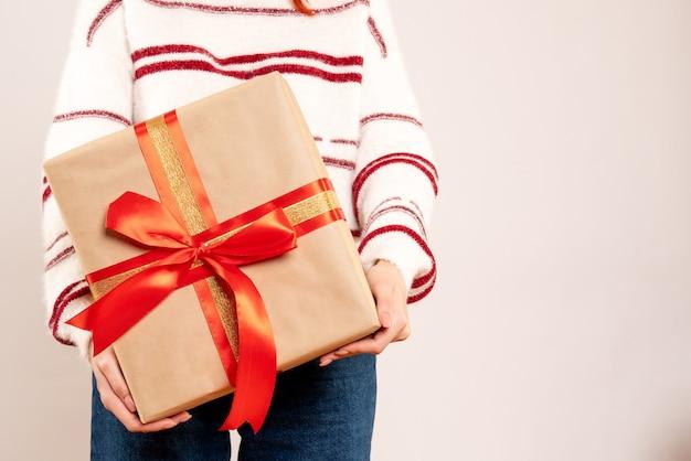 Vorderansicht der jungen frau, die weihnachtsgeschenk auf weißer wand hält