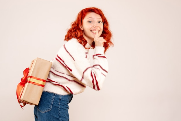 Vorderansicht der jungen frau, die weihnachtsgeschenk hinter ihrem rücken auf weißer wand versteckt