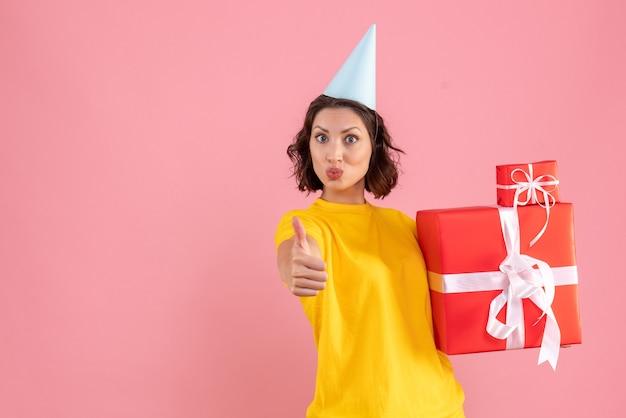 Vorderansicht der jungen frau, die weihnachtsgeschenke an der rosa wand hält