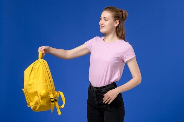 Vorderansicht der jungen frau im rosa t-shirt, das gelben rucksack an der blauen wand hält