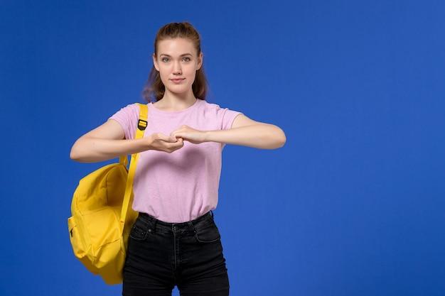 Vorderansicht der jungen frau im rosa t-shirt, das gelben rucksack an der blauen wand trägt