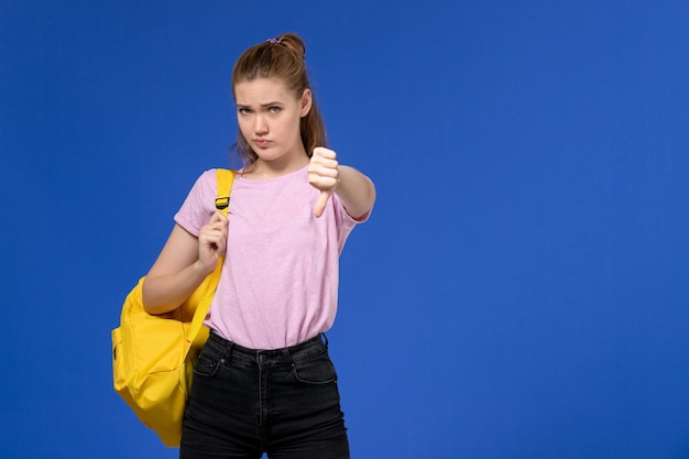 Vorderansicht der jungen frau im rosa t-shirt, das gelben rucksack auf der hellblauen wand trägt