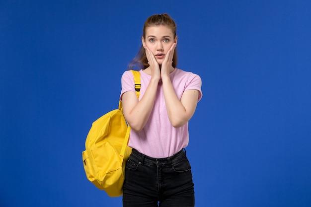 Vorderansicht der jungen frau im rosa t-shirt, das gelben rucksack trägt, der auf der blauen wand aufwirft