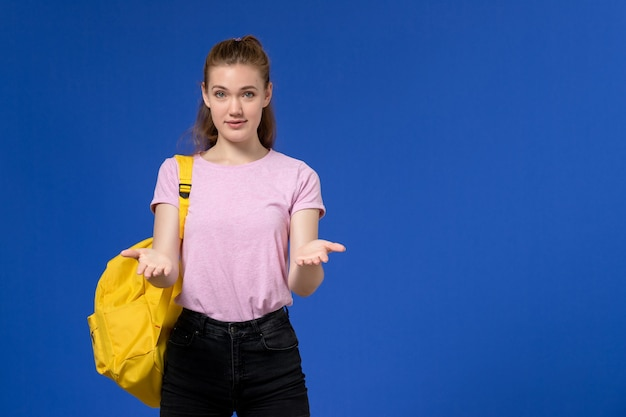 Vorderansicht der jungen frau im rosa t-shirt, das gelben rucksack trägt, der auf der hellblauen wand aufwirft
