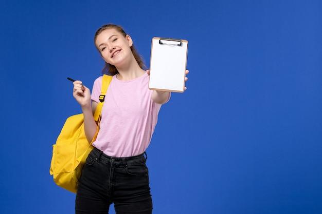 Vorderansicht der jungen frau im rosa t-shirt, das gelben rucksack trägt und notizblock an der blauen wand hält