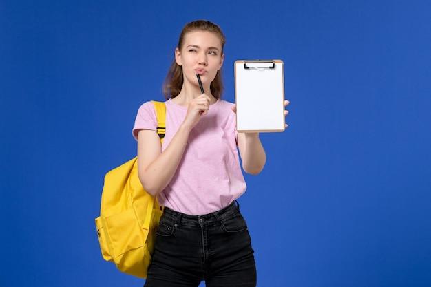 Vorderansicht der jungen frau im rosa t-shirt, das gelben rucksack trägt und notizblock denkt auf blaue wand hält