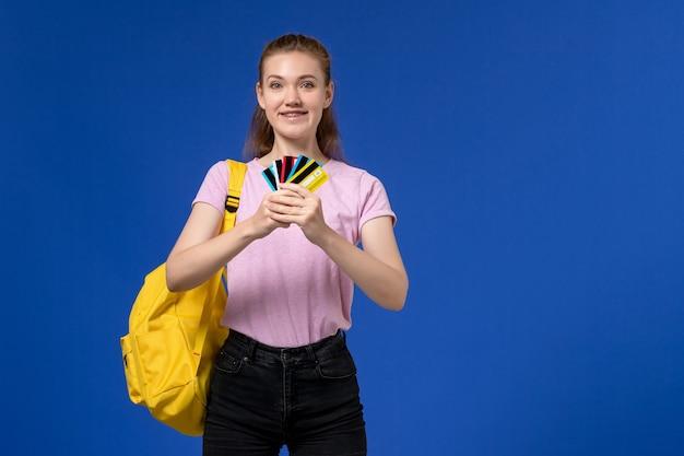 Vorderansicht der jungen frau im rosa t-shirt tragenden gelben rucksack, der verschiedene karten auf blauer wand hält