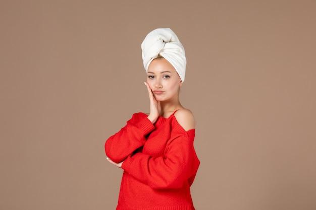 Vorderansicht der jungen frau im roten hemd mit handtuch auf dem kopf braune wand