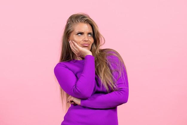 Vorderansicht der jungen frau im schönen lila kleid, die an der rosa wand posiert