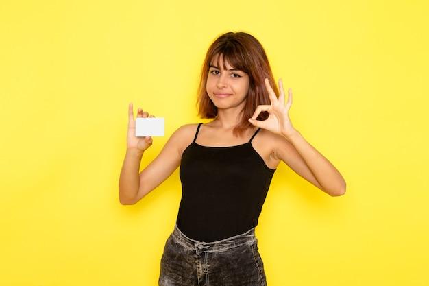 Vorderansicht der jungen frau im schwarzen hemd, das plastikkarte auf hellgelber wand hält