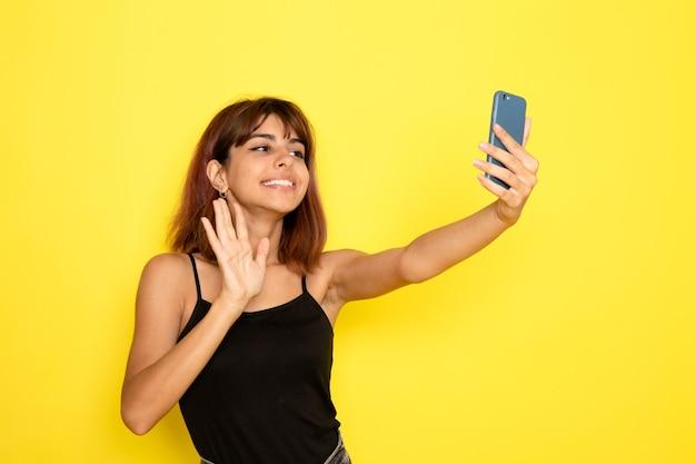 Vorderansicht der jungen frau im schwarzen hemd, das selfie auf gelber wand nimmt