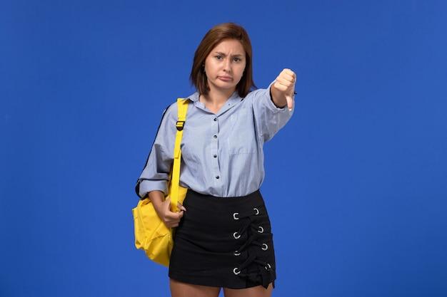 Vorderansicht der jungen frau im schwarzen hemd des blauen hemdes, der gelben rucksack trägt, der im gegensatz zum zeichen auf hellblauer wand zeigt