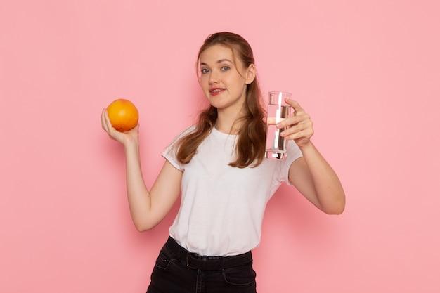 Vorderansicht der jungen frau im weißen t-shirt, das frische grapefruit und glas wasser auf der rosa wand hält