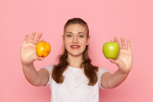 Vorderansicht der jungen frau im weißen t-shirt, das frischen grünen apfel mit pfirsich lächelnd auf hellrosa wand hält