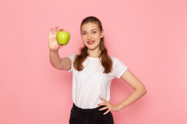 Vorderansicht der jungen frau im weißen t-shirt, das grünen apfel mit lächeln auf hellrosa wand hält