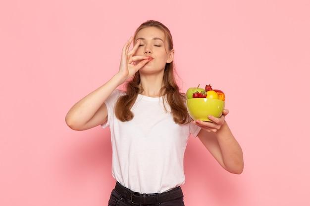 Vorderansicht der jungen frau im weißen t-shirt, das platte mit frischen früchten auf rosa wand hält