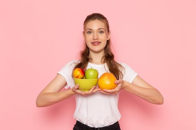Vorderansicht der jungen frau im weißen t-shirt, das platte mit frischen früchten und grapefruit auf der rosa wand hält