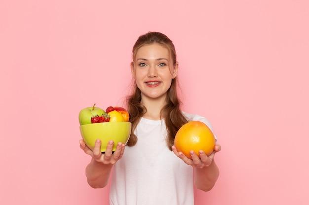 Vorderansicht der jungen frau im weißen t-shirt, das platte mit frischen früchten und grapefruit hält, die auf rosa wand lächeln