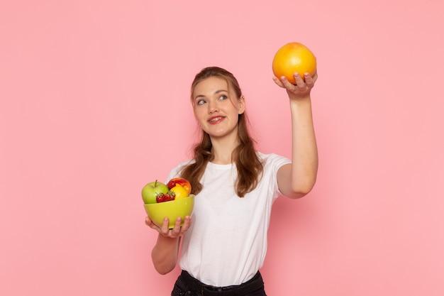 Vorderansicht der jungen frau im weißen t-shirt, das platte mit frischen früchten und grapefruit mit lächeln auf rosa wand hält