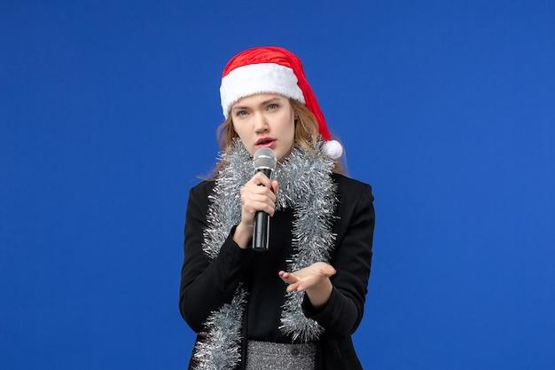 Vorderansicht der jungen frau in der karaoke-party des neuen jahres an der blauen wand