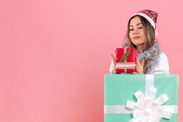 Vorderansicht der jungen frau innerhalb des geschenks, das ein anderes geschenk auf einer rosa wand hält