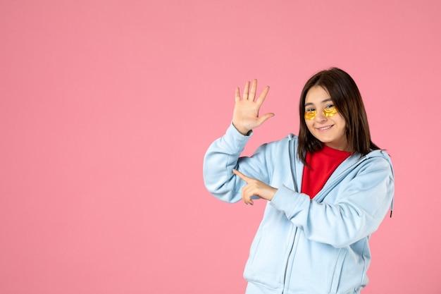 Vorderansicht der jungen frau mit augenklappen auf rosa wand