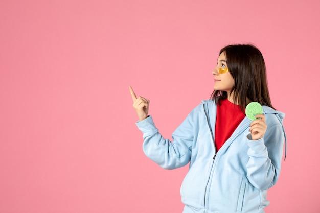 Vorderansicht der jungen frau mit augenklappen und kleinem hautschwamm auf rosa wand