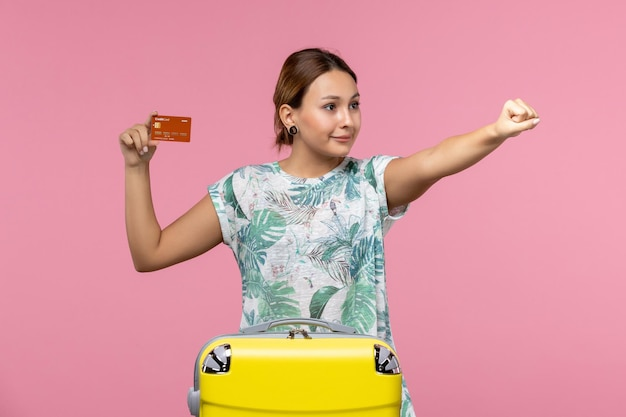 Vorderansicht der jungen frau mit brauner bankkarte an hellrosa wand
