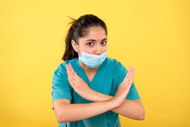 Vorderansicht der jungen frau mit der medizinischen maske, die hände auf gelber wand kreuzt