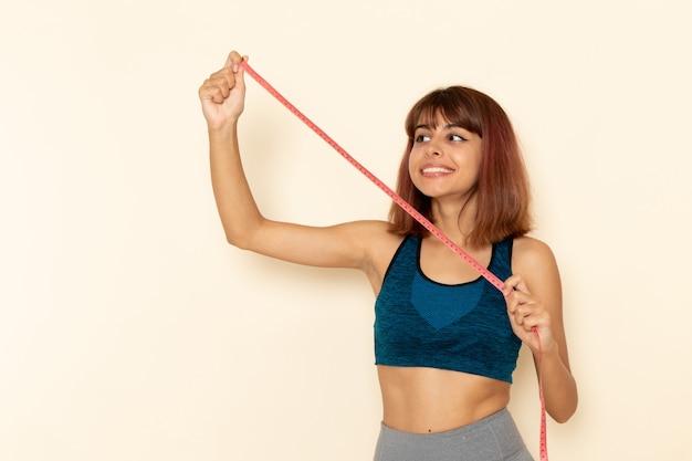 Vorderansicht der jungen frau mit fitem körper im blauen hemd auf hellweißem schreibtischsportgesundheitsmädchenathleten-trainingsübungen
