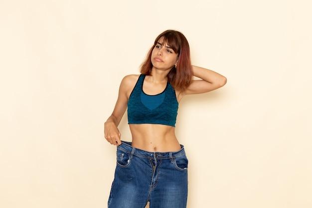 Vorderansicht der jungen frau mit fitem körper im blauen hemd, das ihr gewicht auf der hellweißen wand prüft
