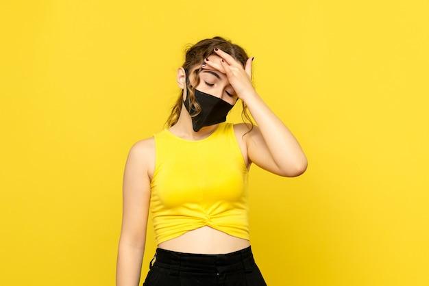 Vorderansicht der jungen frau mit kopfschmerzen auf gelber wand