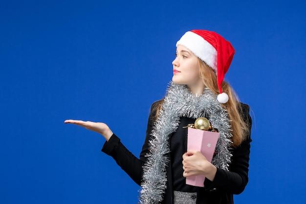 Vorderansicht der jungen frau mit neujahrsbaumspielzeug auf blauer wand